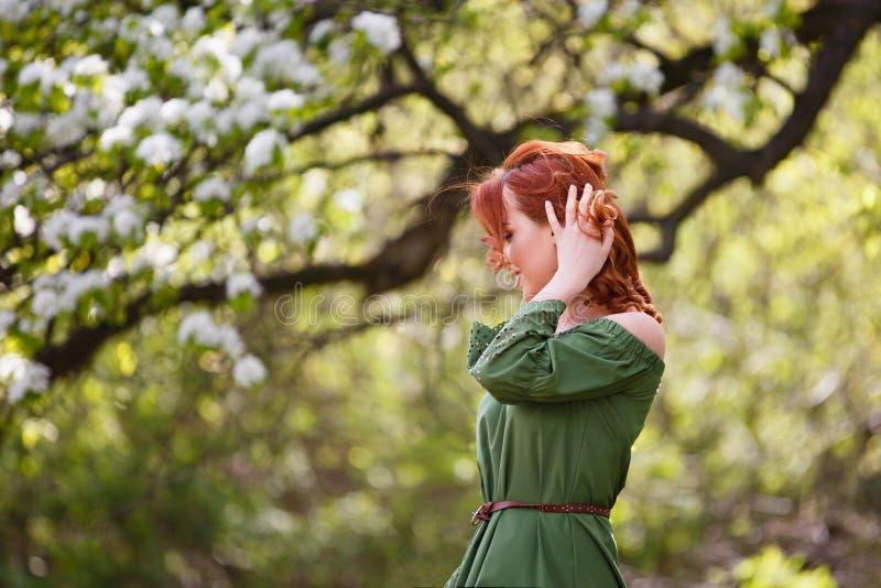 Junge Frau im romantischen grünen Kleid in einem blühenden Apfelgarten lizenzfreie stockbilder
