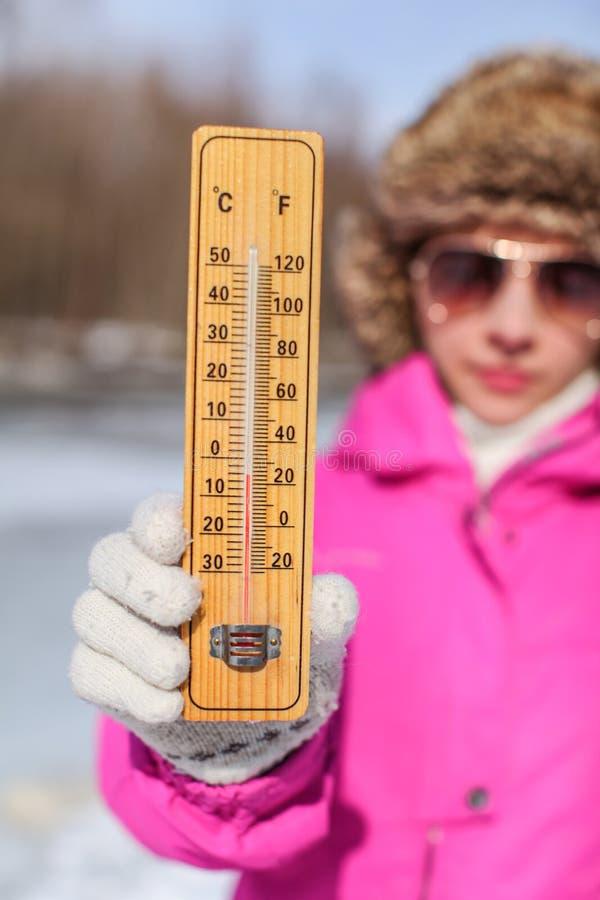 Junge Frau im rosa Winter gehoben, in den Handschuhen und im Pelzhutholdingthermometer, der -5 Grad zeigt Winter/kaltes Tageskomm lizenzfreies stockbild