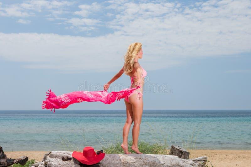 Junge Frau im roten Bikini, der Saronge auf dem Strand hält lizenzfreie stockfotografie