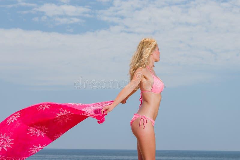 Junge Frau im roten Bikini, der Saronge auf dem Strand hält lizenzfreie stockfotos