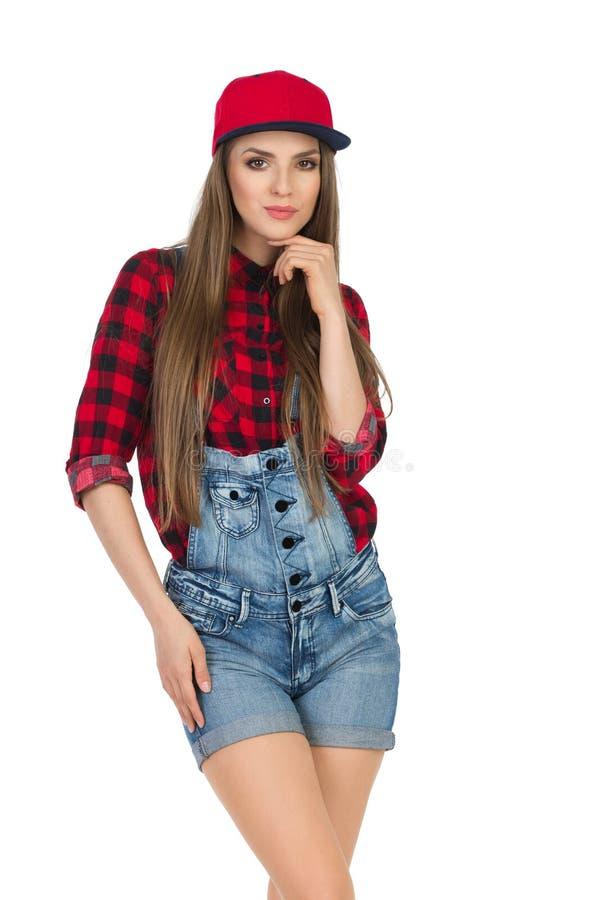 Junge Frau im roten Holzfäller Shirt And Dungarees lizenzfreies stockfoto