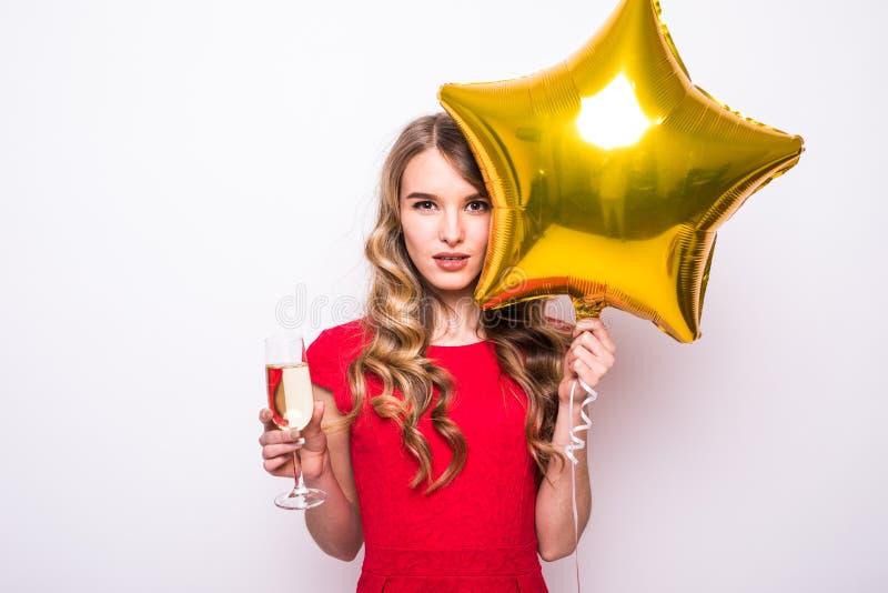 junge Frau im roten Kleid mit lächelndem und trinkendem Champagner des Goldsternförmigem Ballons lizenzfreie stockfotografie