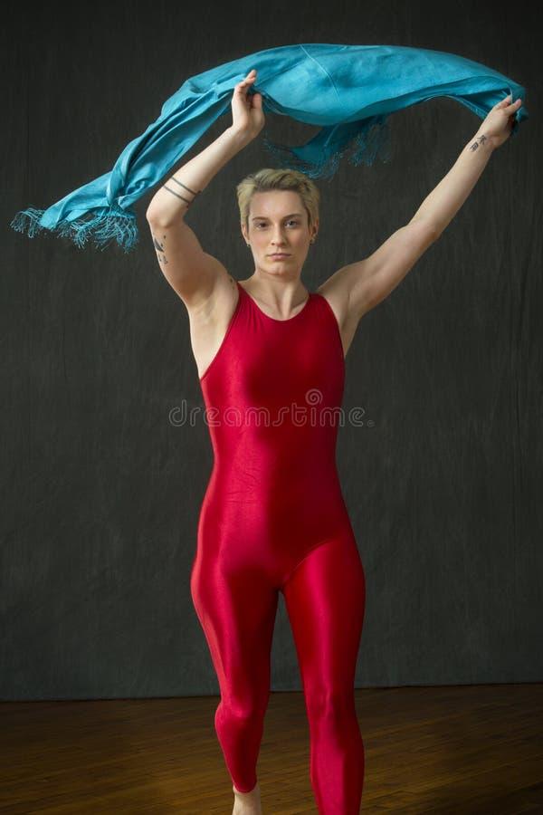 Junge Frau im roten unitard, das einen blauen Schal wellenartig bewegt lizenzfreie stockbilder