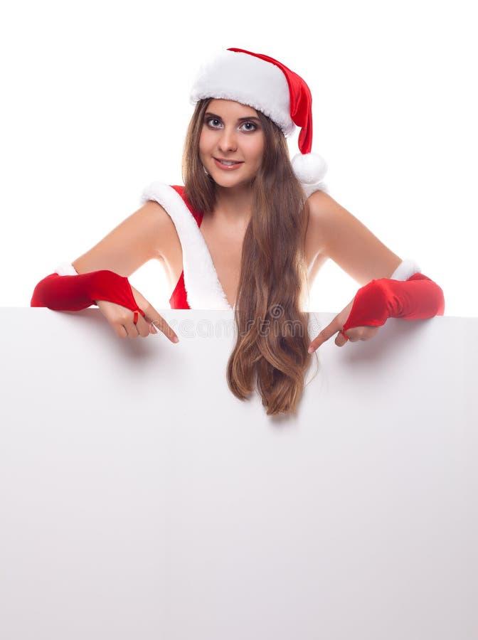 Junge Frau im roten Weihnachtskleid und -hut mit einem leeren billboa lizenzfreie stockfotografie