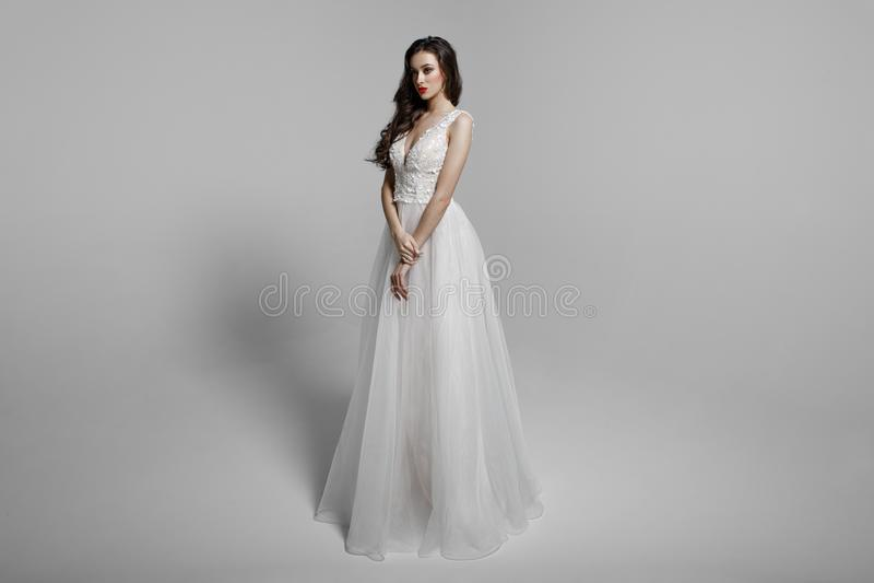 Junge Frau im schönen Kleid, das im Studio sitzt Attraktives kaukasisches Modell, lokalisiert auf einem weißen Hintergrund stockbild