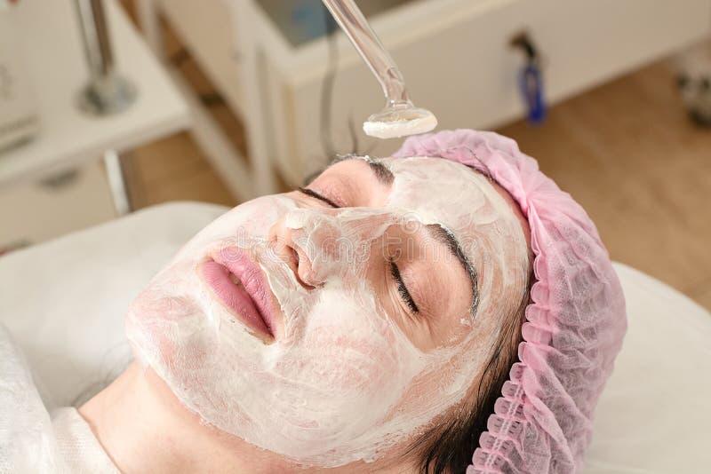 Junge Frau im Schönheitssalon tut das Verjüngen und tont das Verfahren, das auf dem Gesicht darsonval ist stockbild