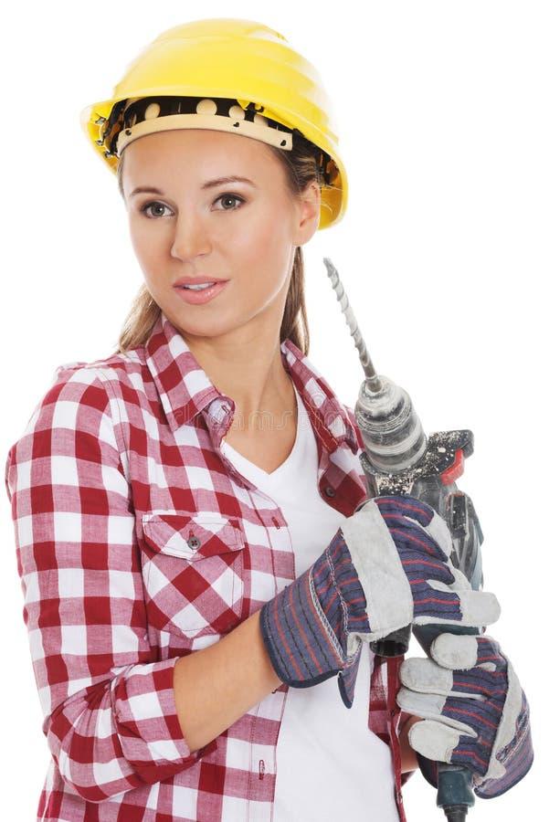 Junge Frau im Schutzhelm und im Jackhammer. lizenzfreie stockbilder
