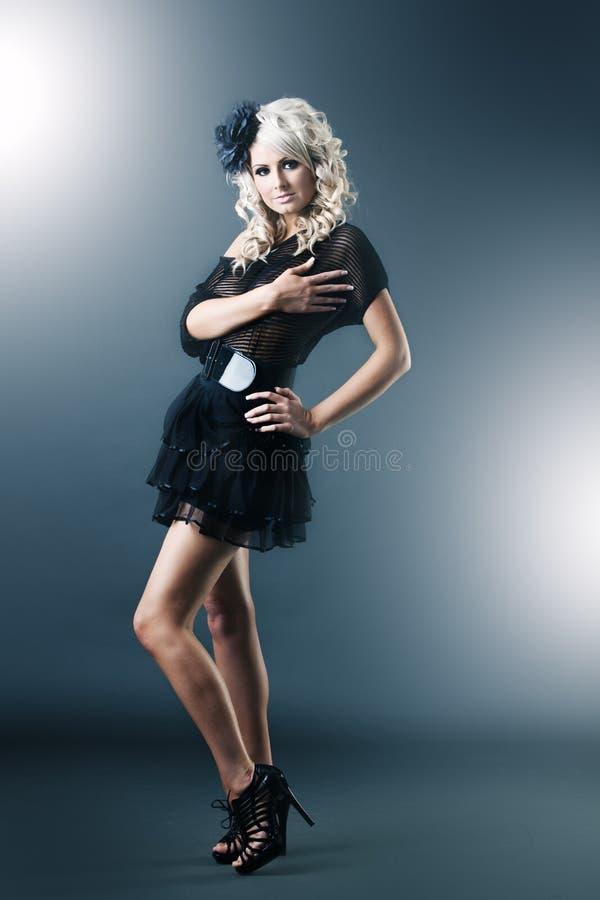 Junge Frau im schwarzem Spitzekleid und -fersen stockfotografie