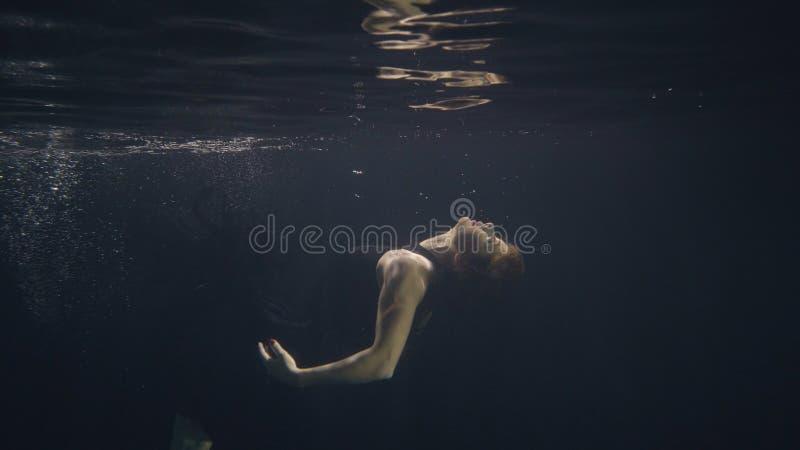 Junge Frau im schwarzen Kleid schwimmend unter Wasser im Pool während Videodreh stockfoto