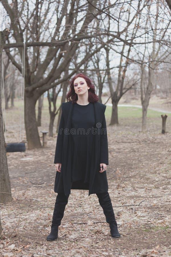 Junge Frau im schwarzen Kleider- und Mantelstand im vollen Körper des Parks schoss Vorderansichtwinter lizenzfreie stockbilder