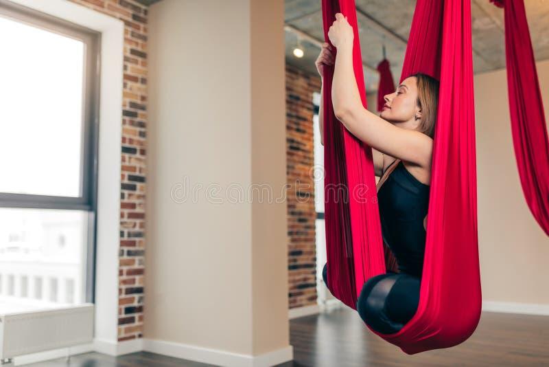 Junge Frau im schwarzen Overall führt Antigravitationsyogaübung im Yogastudio durch lizenzfreie stockfotos