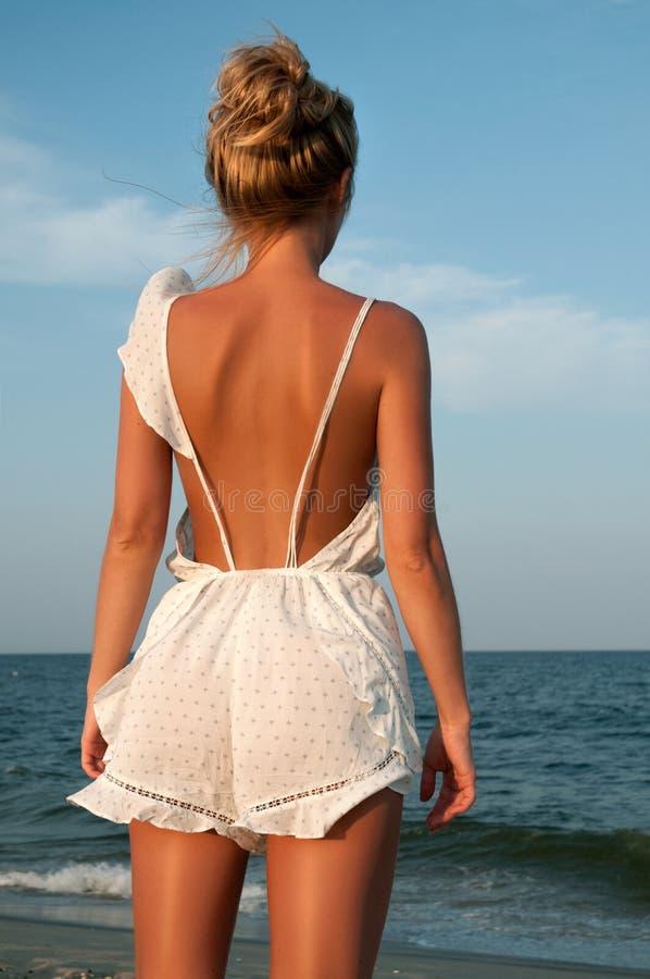 Junge Frau im Sommerkleid, das auf einem Strand steht und zum Meer schaut stockbild