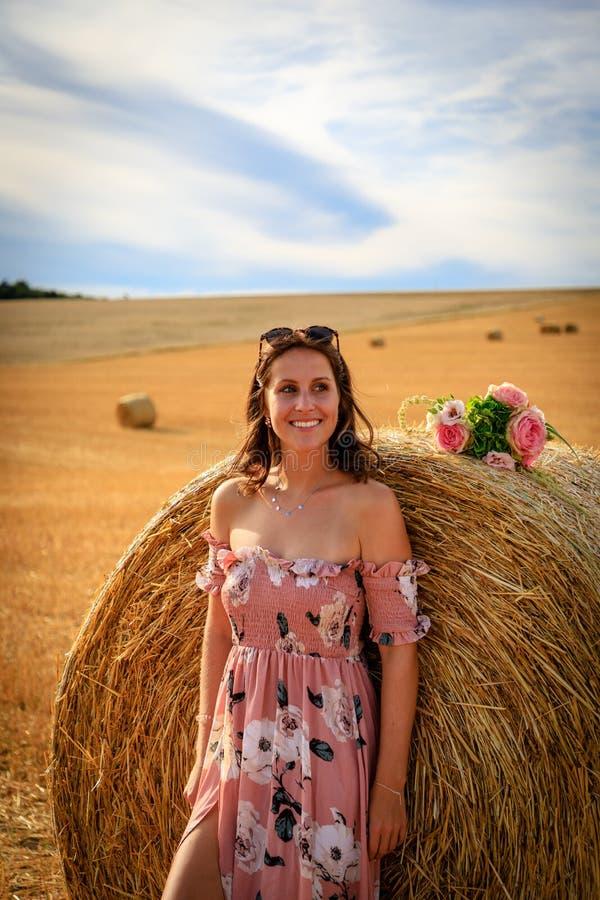 Junge Frau im Sommerkleid lehnt sich an einem Strohballen stockbilder