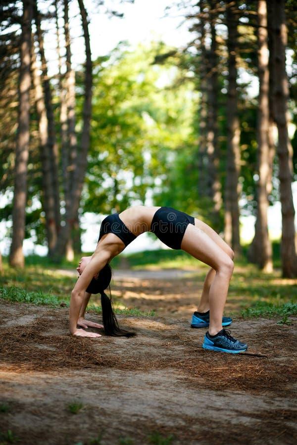 Junge Frau im sportwear, welches die Stärke ausgeübt im Sommerpark tut Sportübungsfreien stockbilder