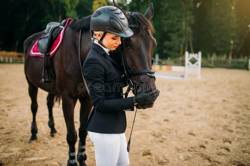 Junge Frau im Sturzhelm umarmt Pferd, Reiten stockbilder