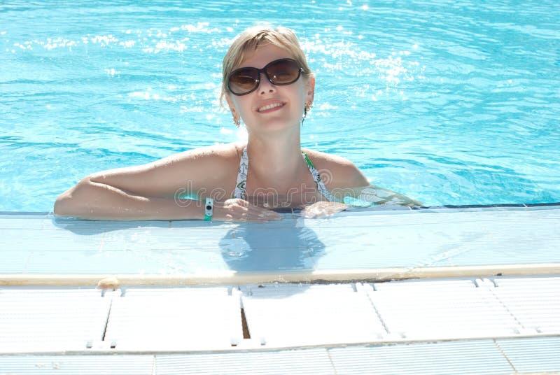 Junge Frau im Swimmingpool stockbild