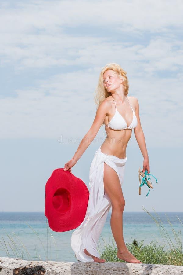 Junge Frau im weißen Bikini, der Saronge auf dem Strand hält lizenzfreie stockbilder