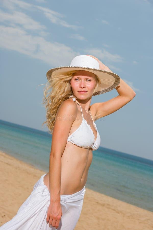 Junge Frau im weißen Bikini, der Saronge auf dem Strand hält stockfotografie
