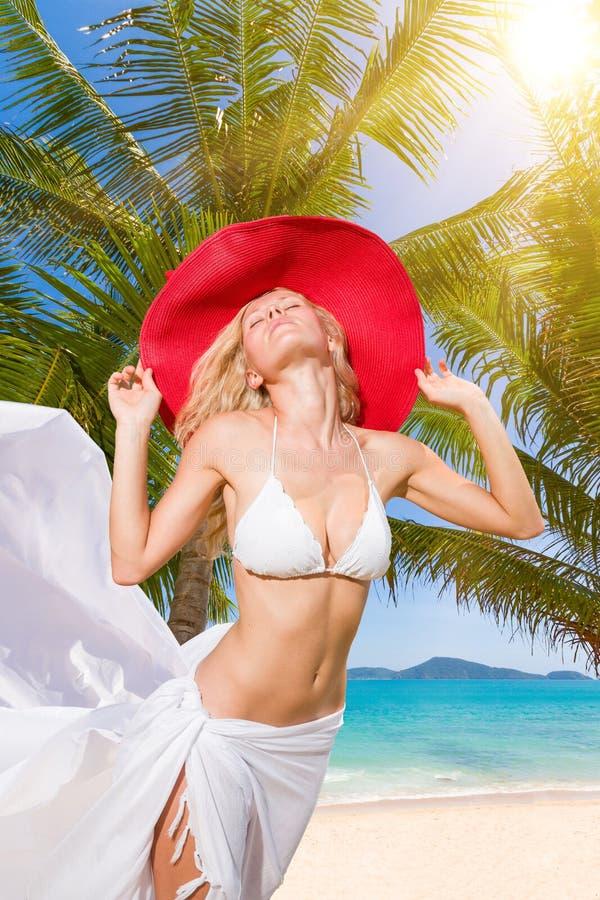 Junge Frau im weißen Bikini, der Saronge auf dem Strand hält stockfotos
