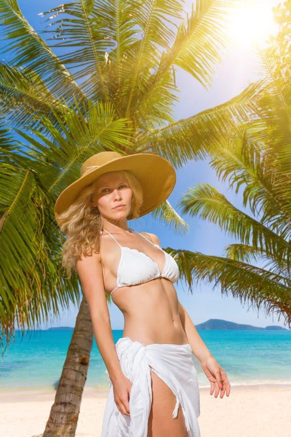 Junge Frau im weißen Bikini, der Saronge auf dem Strand hält lizenzfreie stockfotos