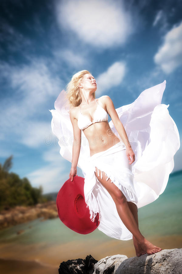 Junge Frau im weißen Bikini, der Saronge auf dem Strand hält stockbilder