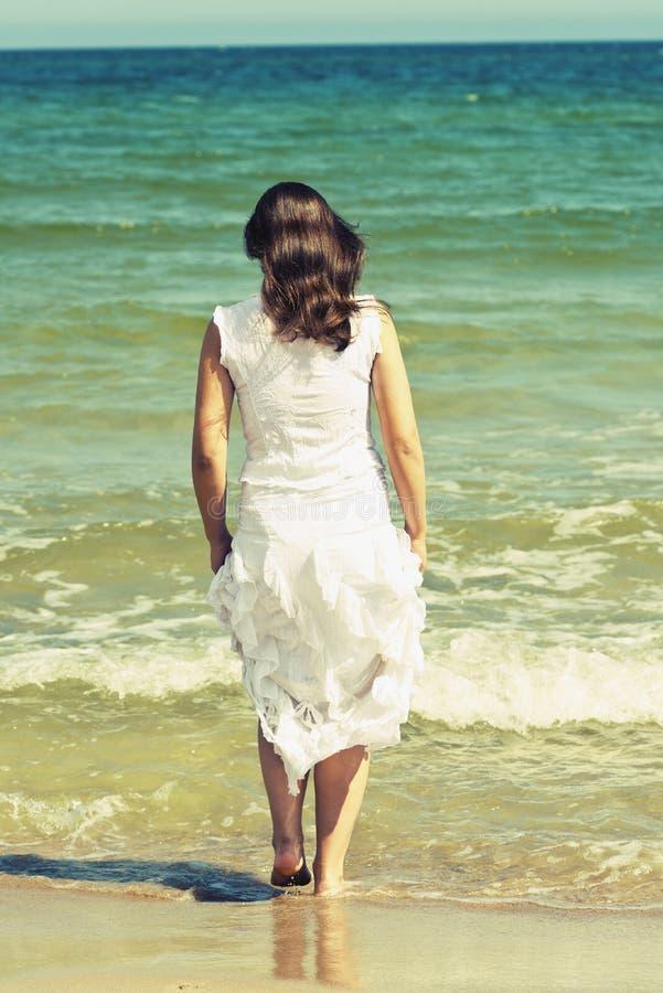 Junge Frau im weißen Kleid gehend auf den Strand lizenzfreies stockfoto