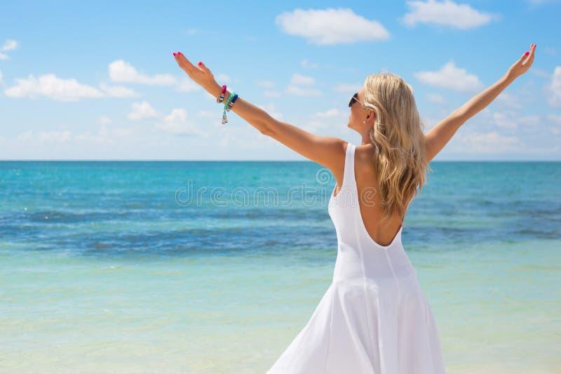Junge Frau im weißen Kleid Sommertag auf dem Strand genießend lizenzfreie stockbilder