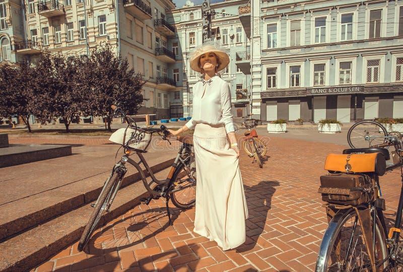 Junge Frau im weißen Weinlesekleid, das mit altem Fahrrad vor Beginn Festival Retro- Kreuzfahrt steht stockfoto
