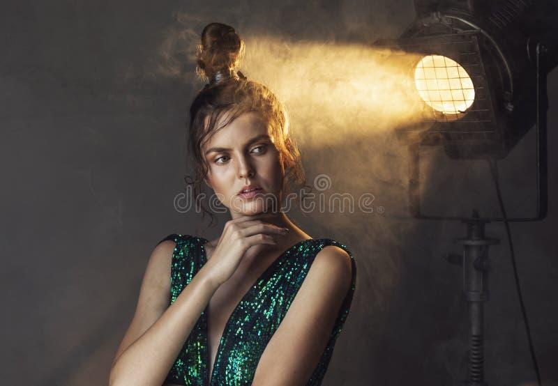 Junge Frau im Weinlese-Kleid, das im Scheinwerfer steht lizenzfreies stockfoto