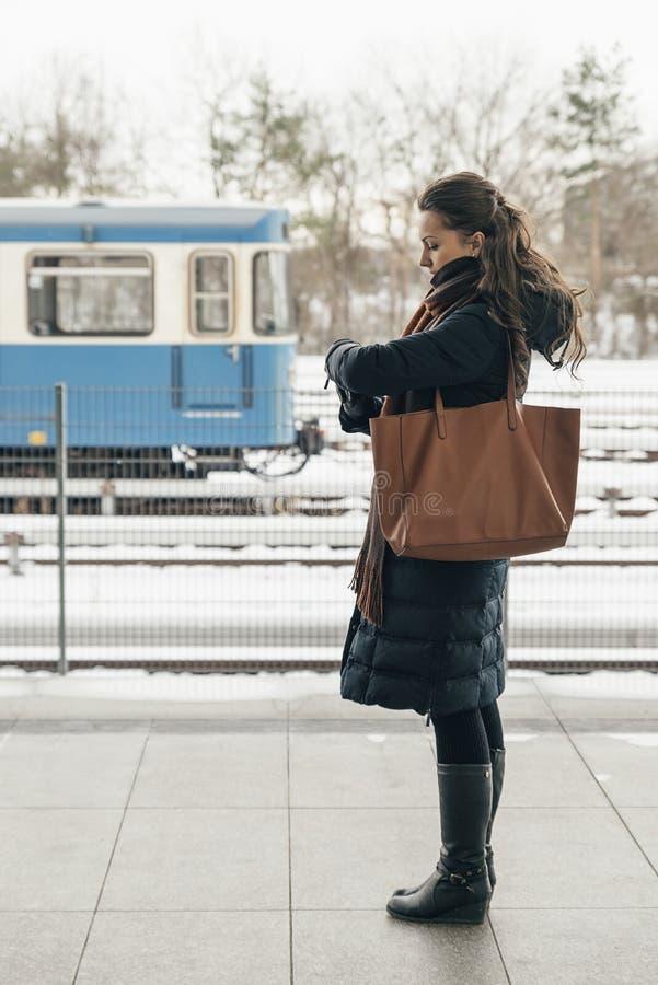 Junge Frau im Wintermantel, der ihren Uhrwartezug sucht stockfoto