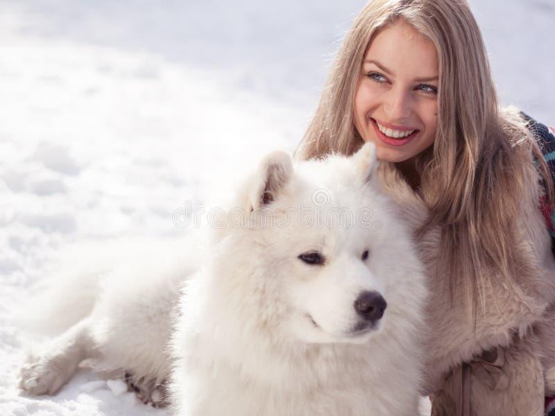 Junge Frau im Winterpark mit Hund stockfoto