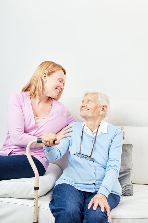 Junge Frau interessiert sich liebevoll für einen älteren Bürger lizenzfreies stockbild