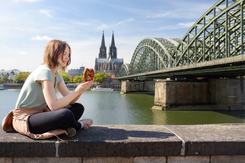 Junge Frau isst die traditionelle Brezel, die herein auf Damm von Rhein auf Hintergrund von Köln-Kathedrale und von Hohenzollern- lizenzfreie stockfotografie