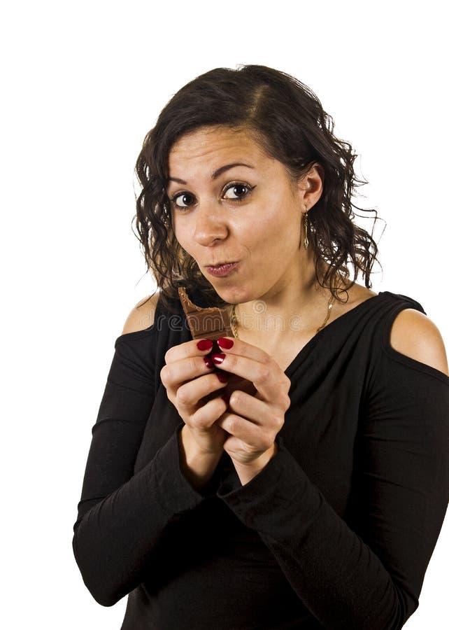 Junge Frau isst Schokolade lizenzfreies stockbild