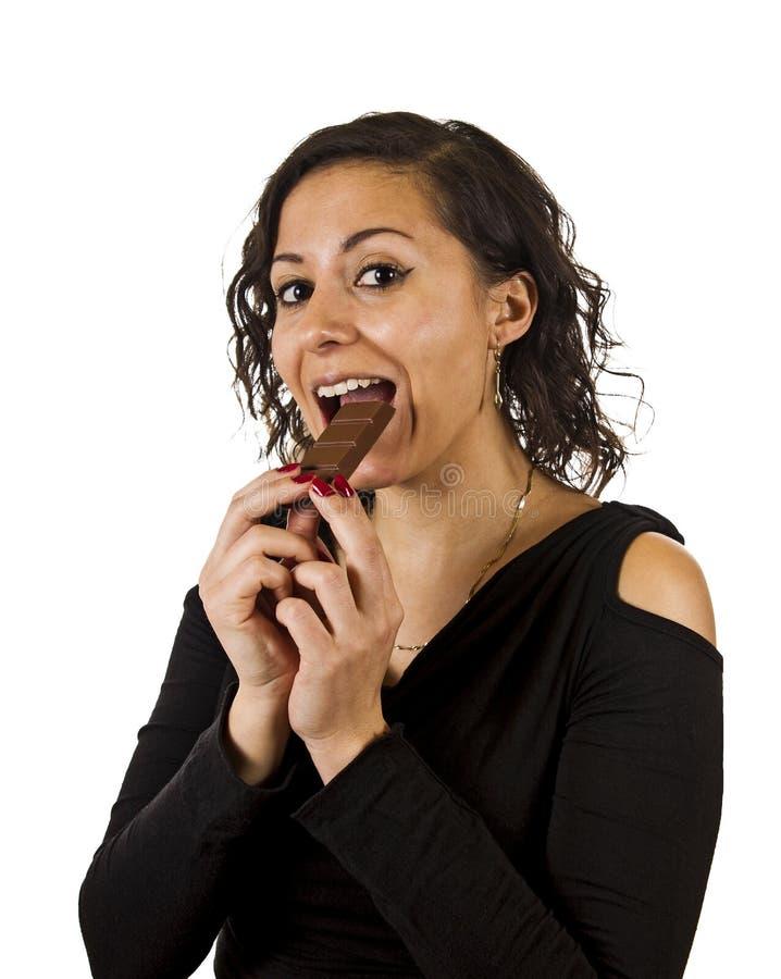 Junge Frau isst Schokolade stockfotografie