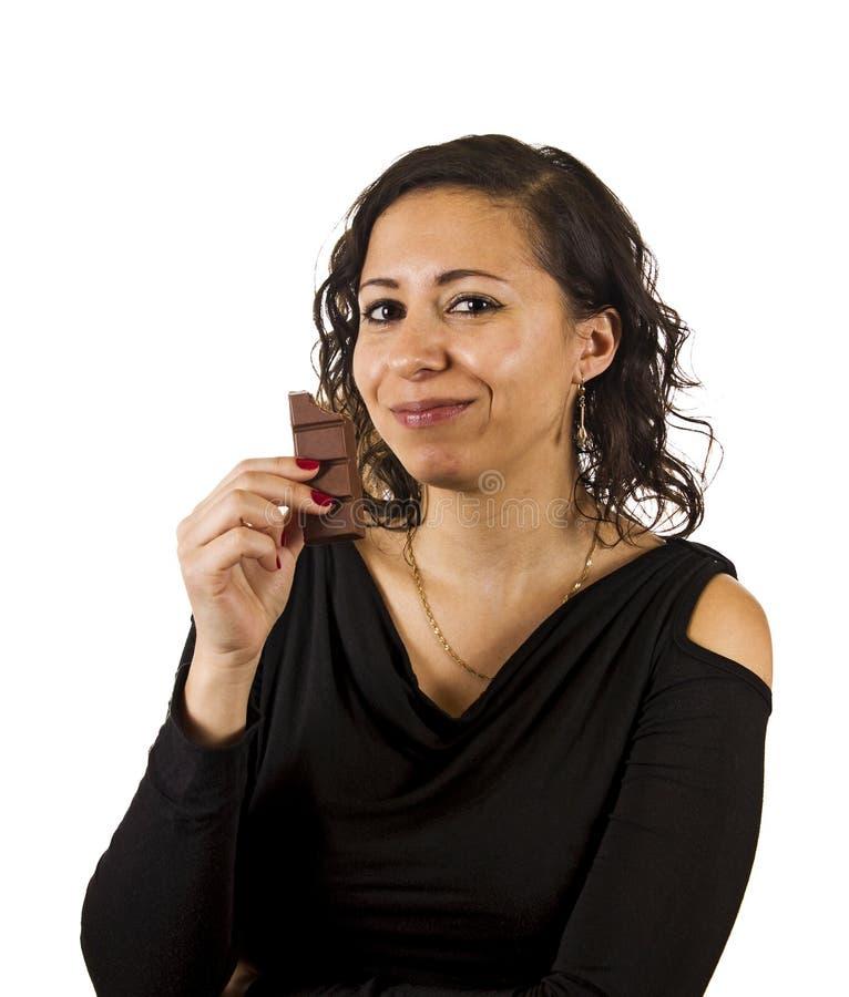 Junge Frau isst Schokolade lizenzfreie stockbilder