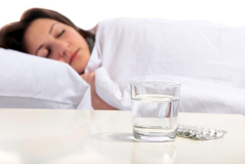 Junge Frau ist im Bett krank stockbilder
