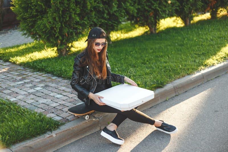 Junge Frau - Jugendlicher mit Skateboard haben einen Rest und das Essen Pizzazum Mitnehmenim Freien in der Straße stockbilder