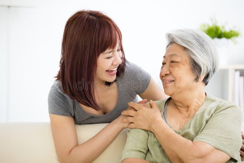Junge Frau kümmert sorgfältig sich um alter Frau stockbilder