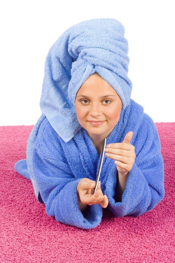 Junge Frau kleidete blaue Bademantel- und Tucharchivierungsnägel lizenzfreies stockfoto