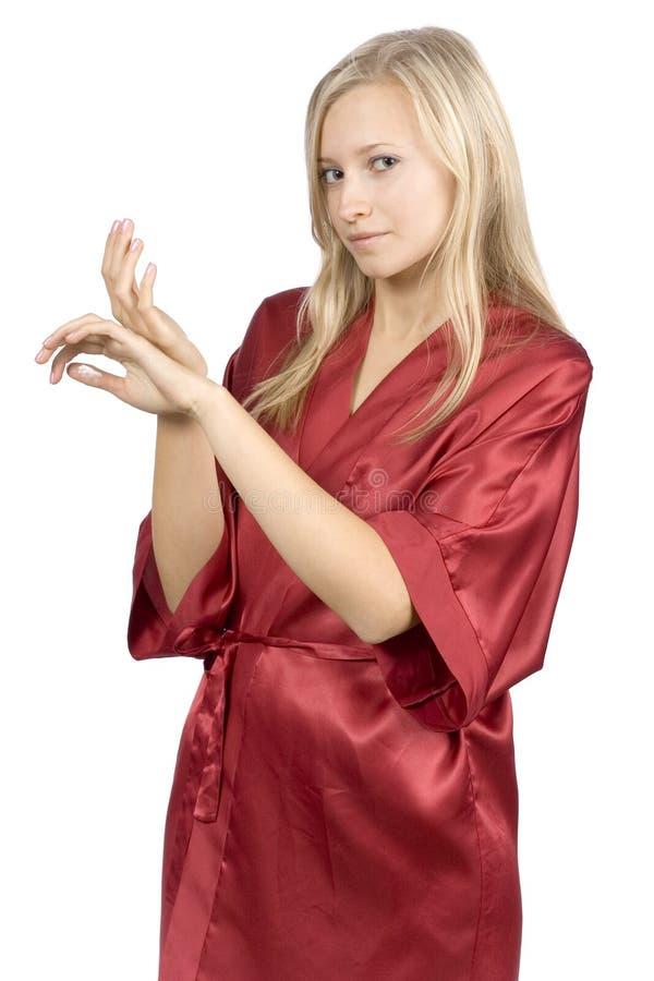 Junge Frau kleidete roten Bademantel mit Sahne auf ihren Händen lizenzfreie stockbilder