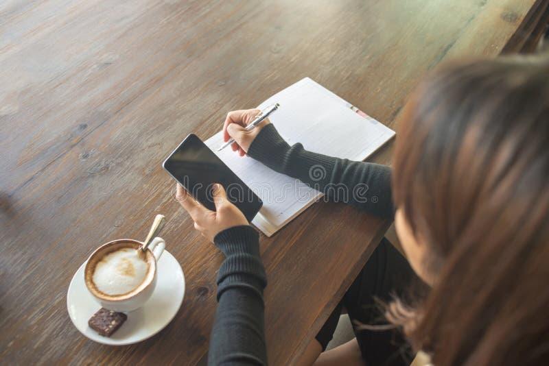Junge Frau klopfender Smartphone durch die linke Hand, schreibend durch rechte Hand lizenzfreies stockbild