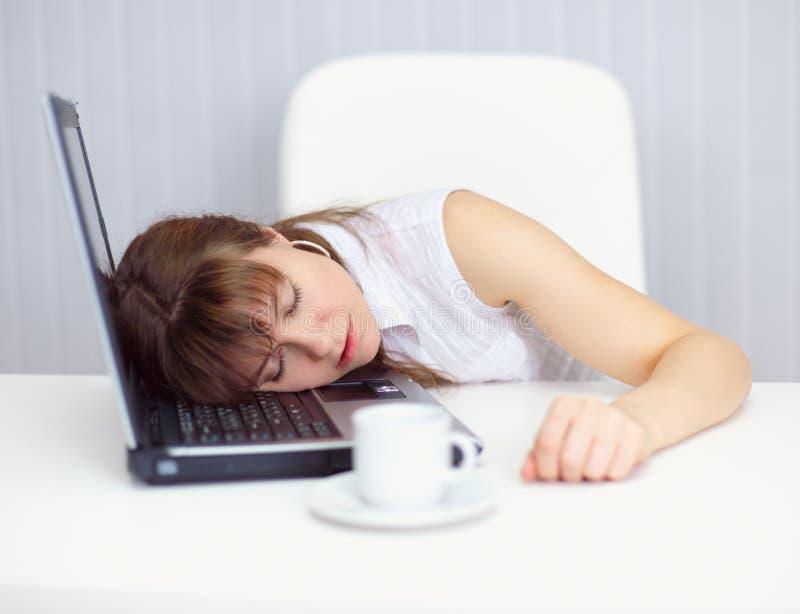 Junge Frau komisch schlafend auf Tastatur am Tisch stockbild