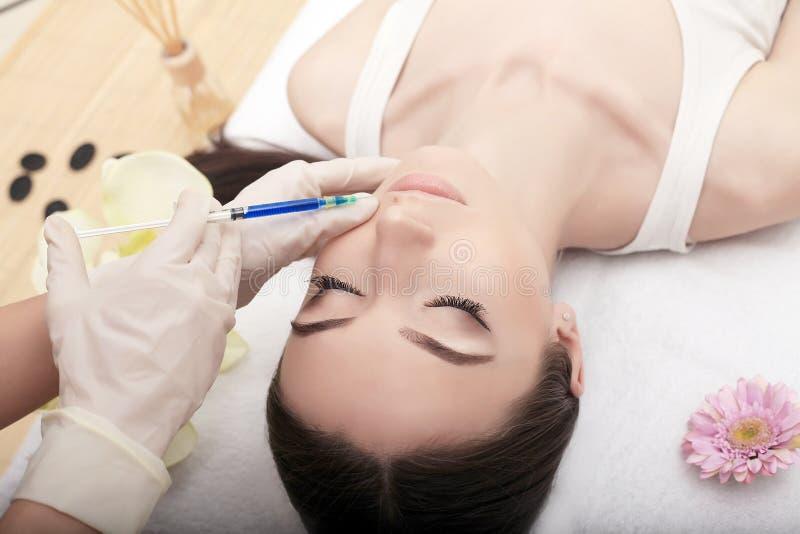 Junge Frau kommt Einspritzung in ihre Stirn Sie sitzt in Doktorbüro und entspannt sich stockfotografie