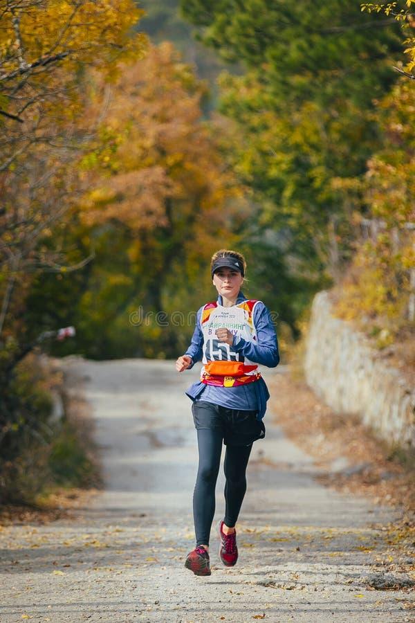 Junge Frau läuft über Straße im Herbstwald stockfotos