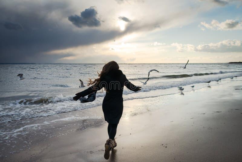Junge Frau läuft entlang die Küste des Ozeans hinter die Vögel lizenzfreie stockfotos
