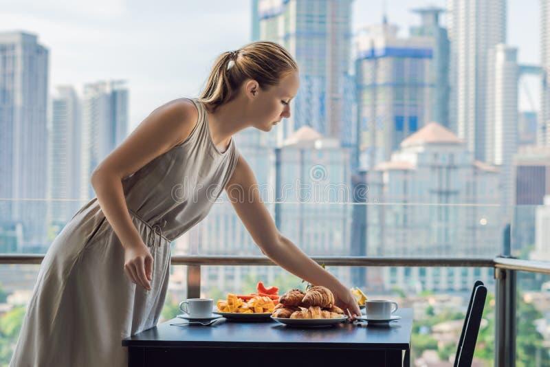 Junge Frau legt auf eine Tabelle Frühstückstisch mit der Kaffeefrucht und -brot croisant auf einem Balkon gegen den Hintergrund lizenzfreie stockfotos