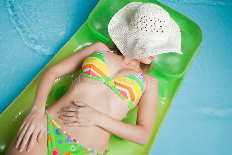 Junge Frau liegt auf einer aufblasbaren Matratze lizenzfreies stockbild