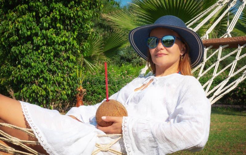 Junge Frau liegt in einer Hängematte mit Coconut-Cocktail stockbild