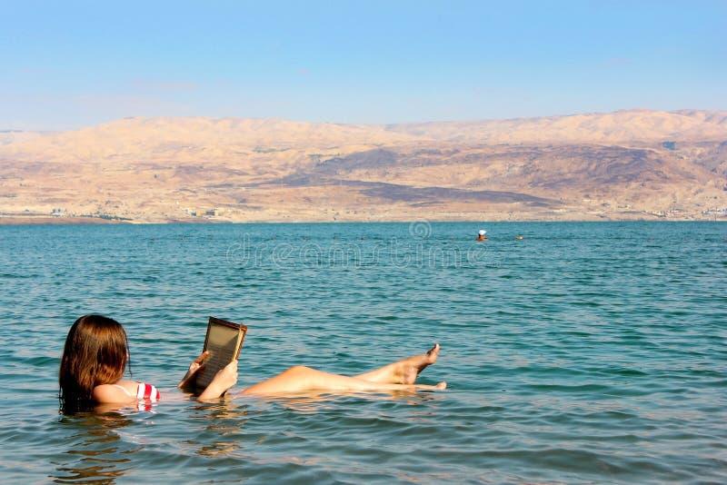 Junge Frau liest ein Buch, das in das Tote Meer in Israel schwimmt lizenzfreies stockbild
